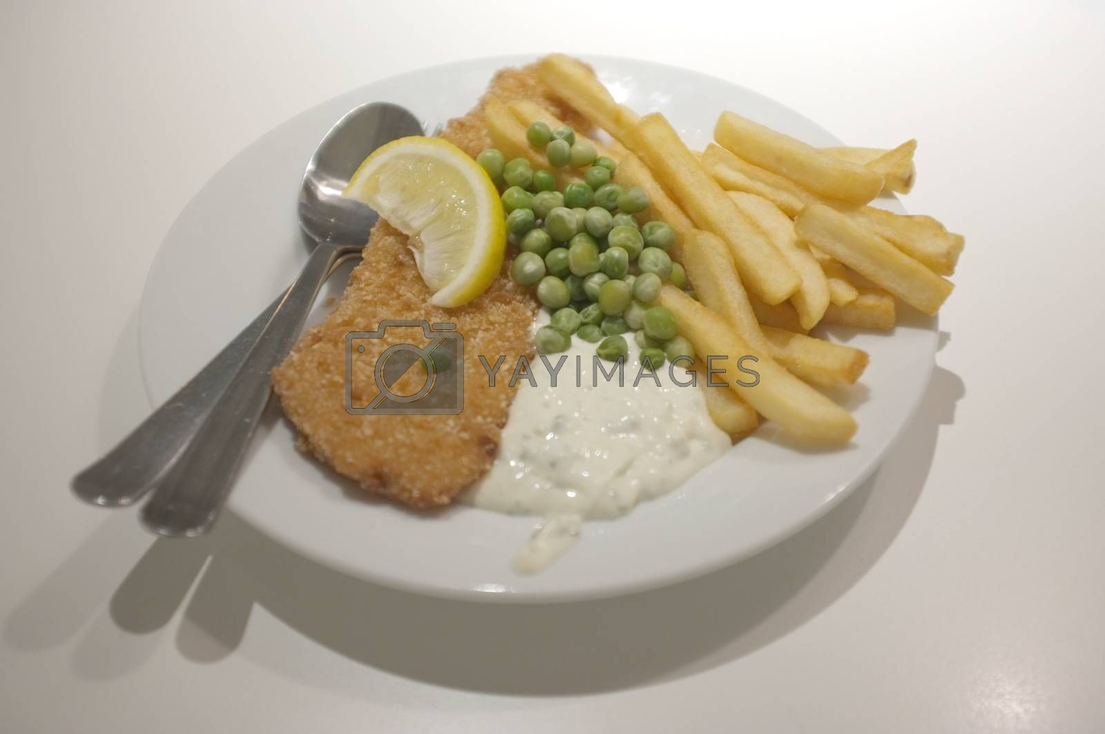 Fish and chips on a dish .