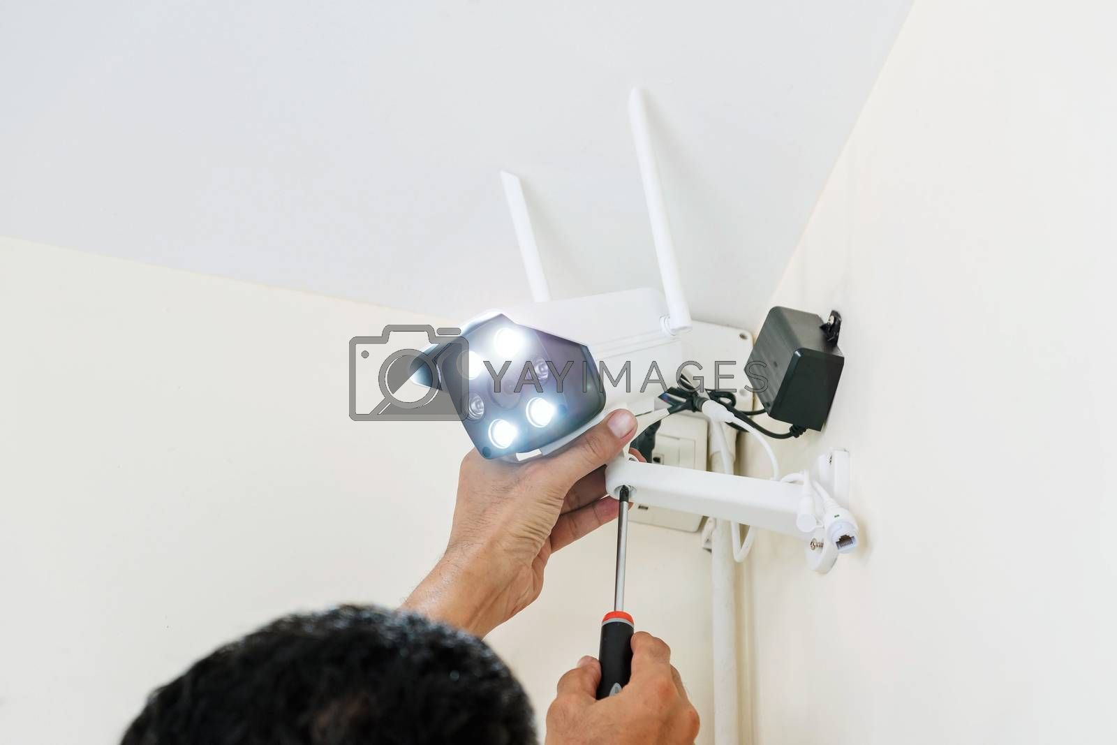 Technicians are installing wireless CCTV cameras on the walls of the house for security purposes.
