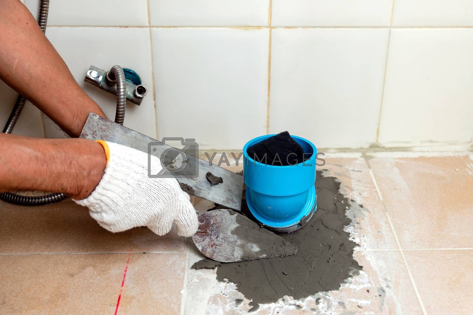 Construction workers are using plastering tools around the PVC pipe to drain the waste inside the bathroom.