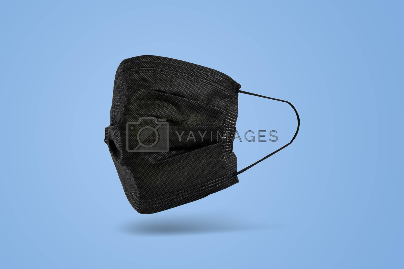 Black sanitary napkin mask for preventing spreading and respiratory infections isolated on pastel color background, Social distancing and stop Coronavirus Covid-19 concept.