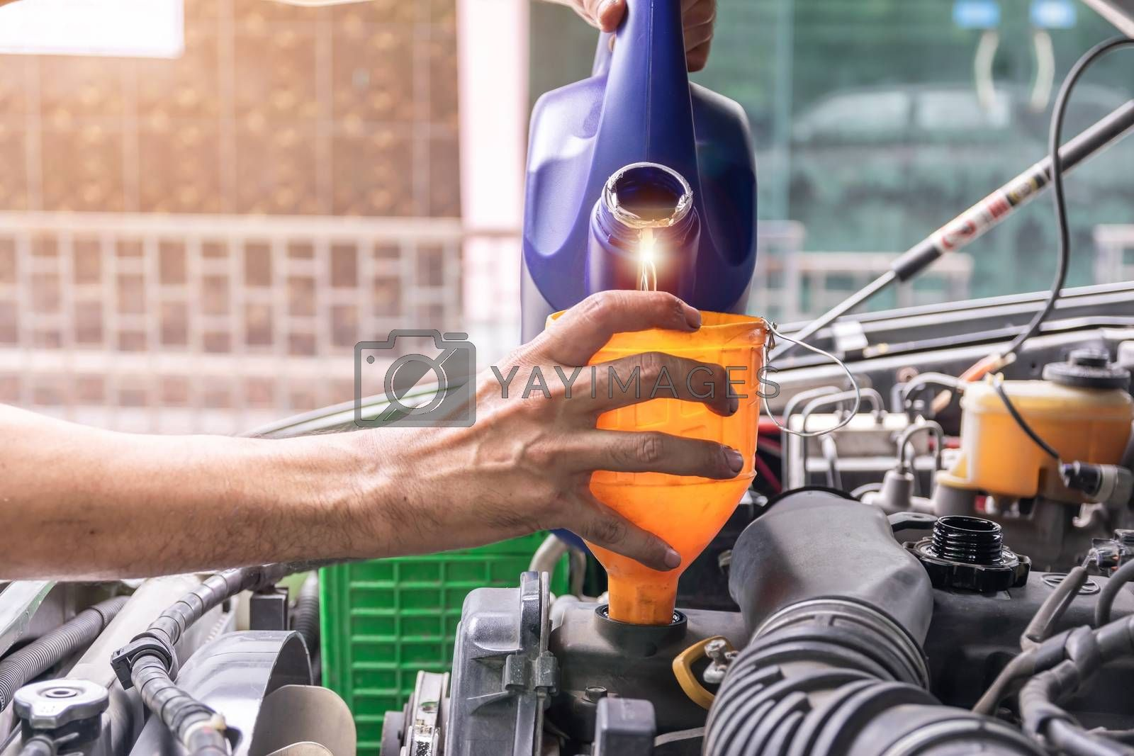 Auto mechanic is filling up the car's engine oil inside the auto repair center, the auto industry and garage ideas.