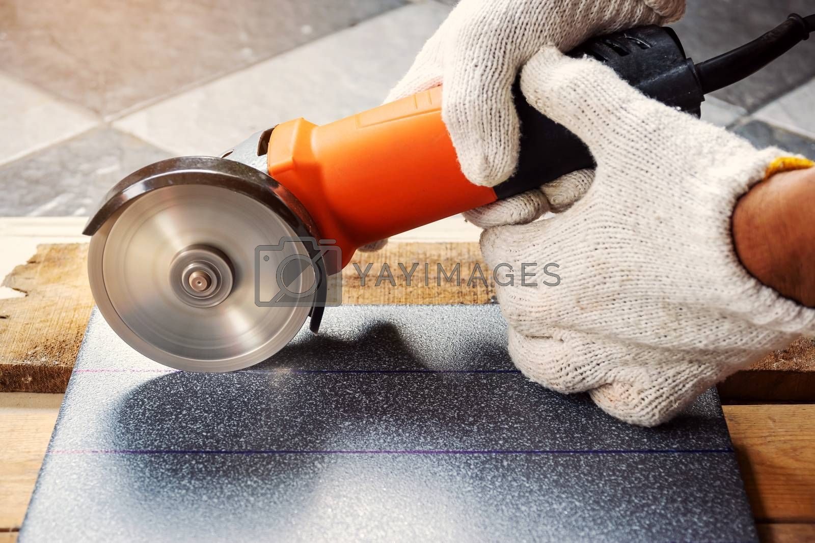 Construction worker wearing white cloth gloves was cutting the tiles with an electric grinder.