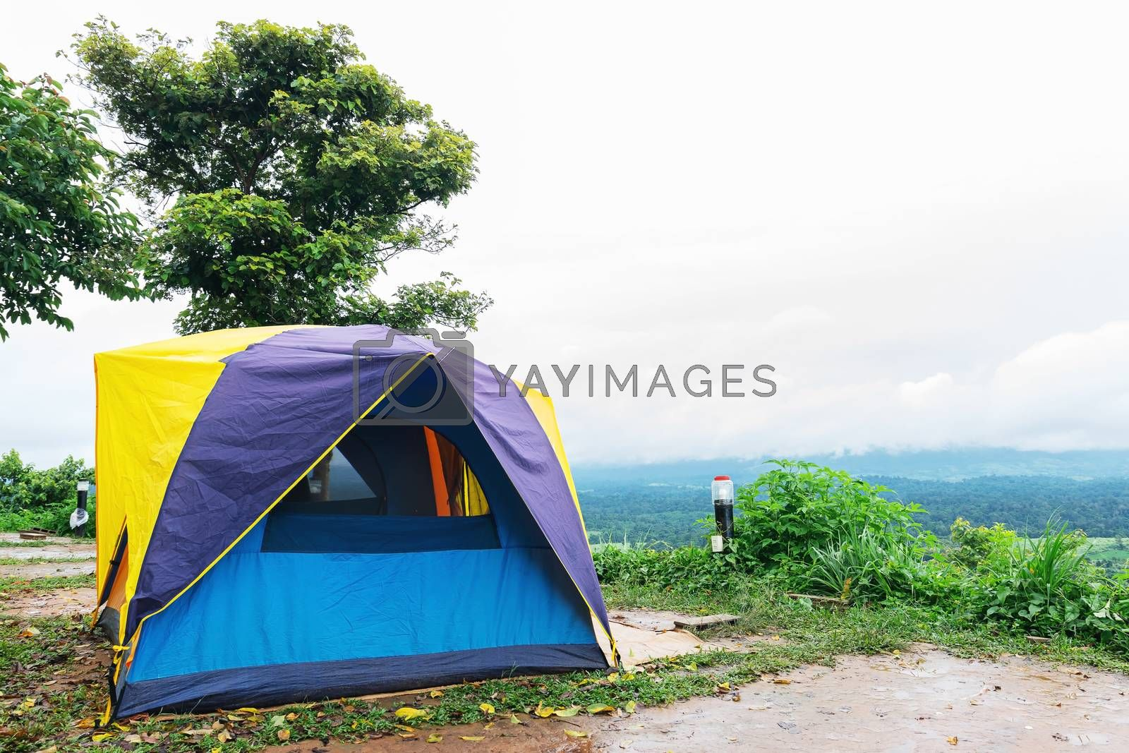 Camping tent that is set up at the highest point of a high mountain with a backdrop of sky and mountains.