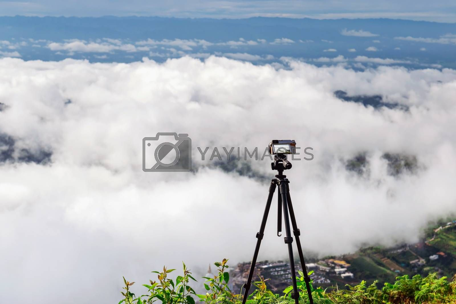 Set a digital camera on a tripod to capture the view of the sky, clouds and mountains.