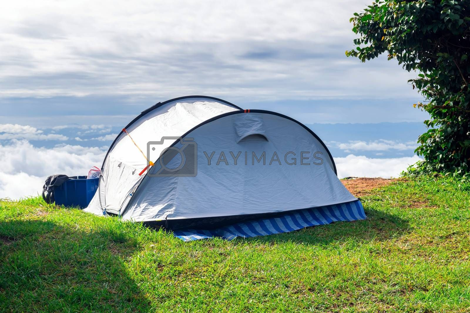 Closeup a camping tent that is set up on a grass field at the highest point of a high mountain with a backdrop of sky and clouds.