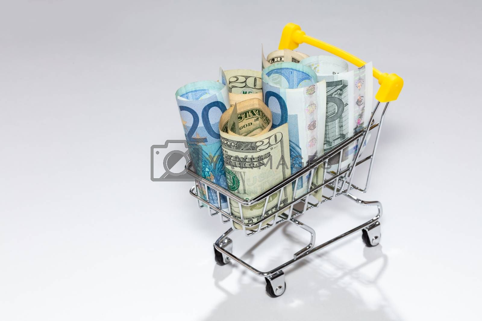 Closeup of a shopping cart full of euro and dollar bills isolated on white background. Concepts of loan, investment, pension, saving money, financing, collateral, debt, mortgage, financial crisis.