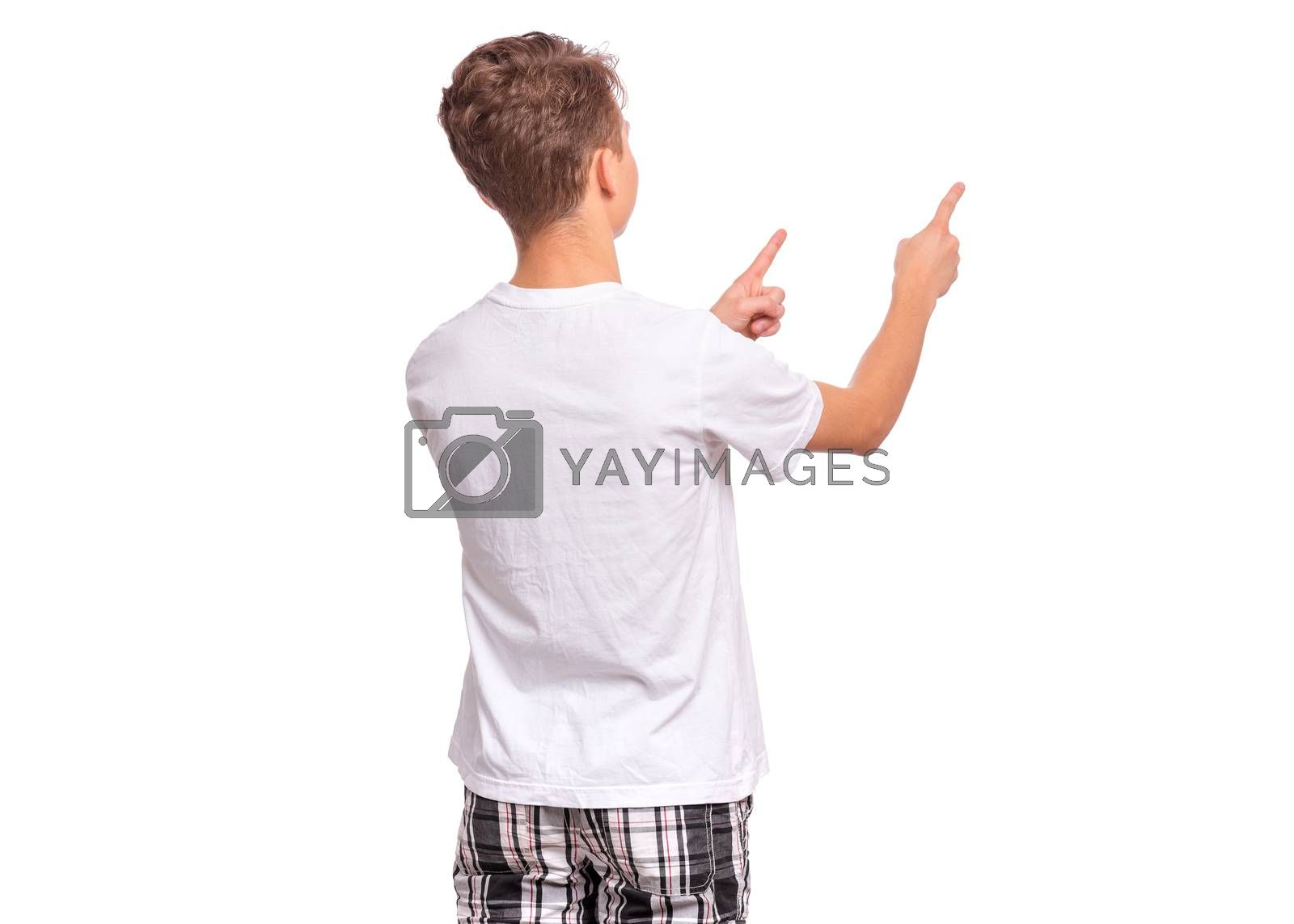 Back view. Teen boy pointing finger away at copyspace, isolated on white background. Teenager pointing fingers at something - rear view. Child in white t-shirt.