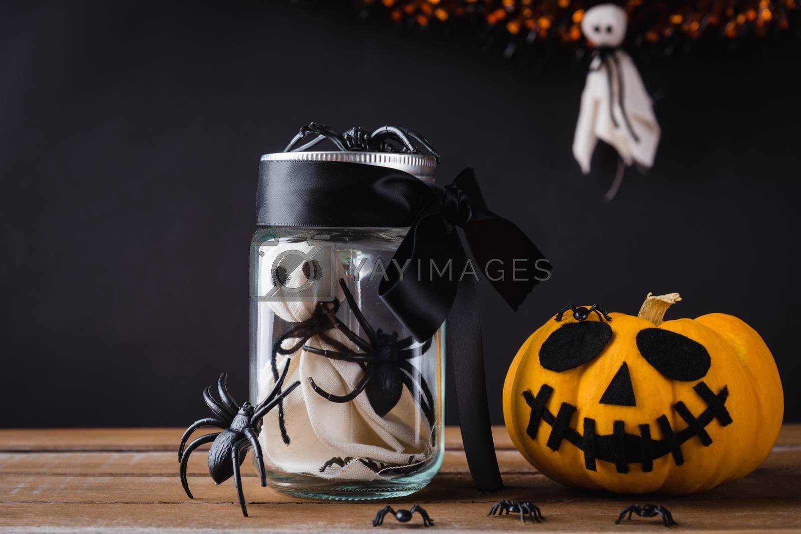 Funny Halloween day decoration party, The white ghost scary face and black spider in jar glass and pumpkin out side on wooden table, studio shot isolated on black background, Happy holiday concept