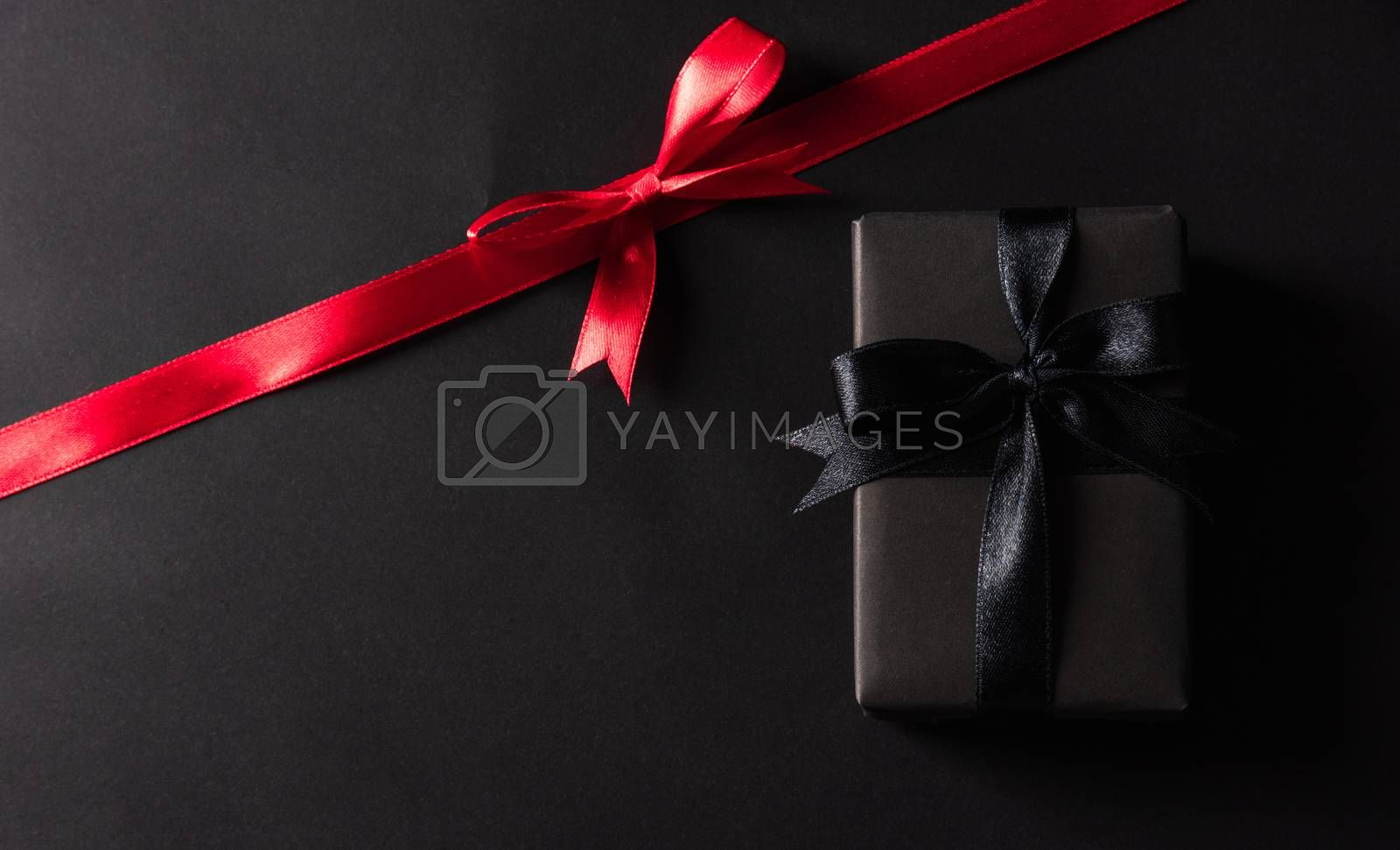 Black Friday Sale concept, Top view of gift box wrapped black paper and black bow ribbon press, studio shot on and having red ribbon across a dark background