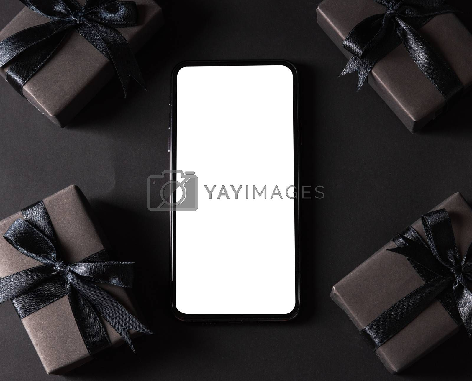 Black Friday sale shopping concept, Top view of gift box wrapped black paper and black bow ribbon present around smartphone blank screen, studio shot on dark background