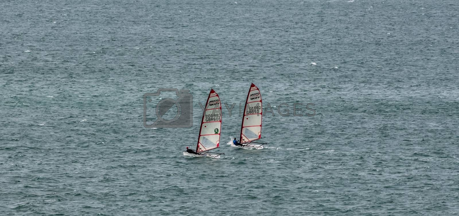 Portland Harbor, UK - July 1, 2020: Two racing Musto Skiff boats sailing in the harbor.