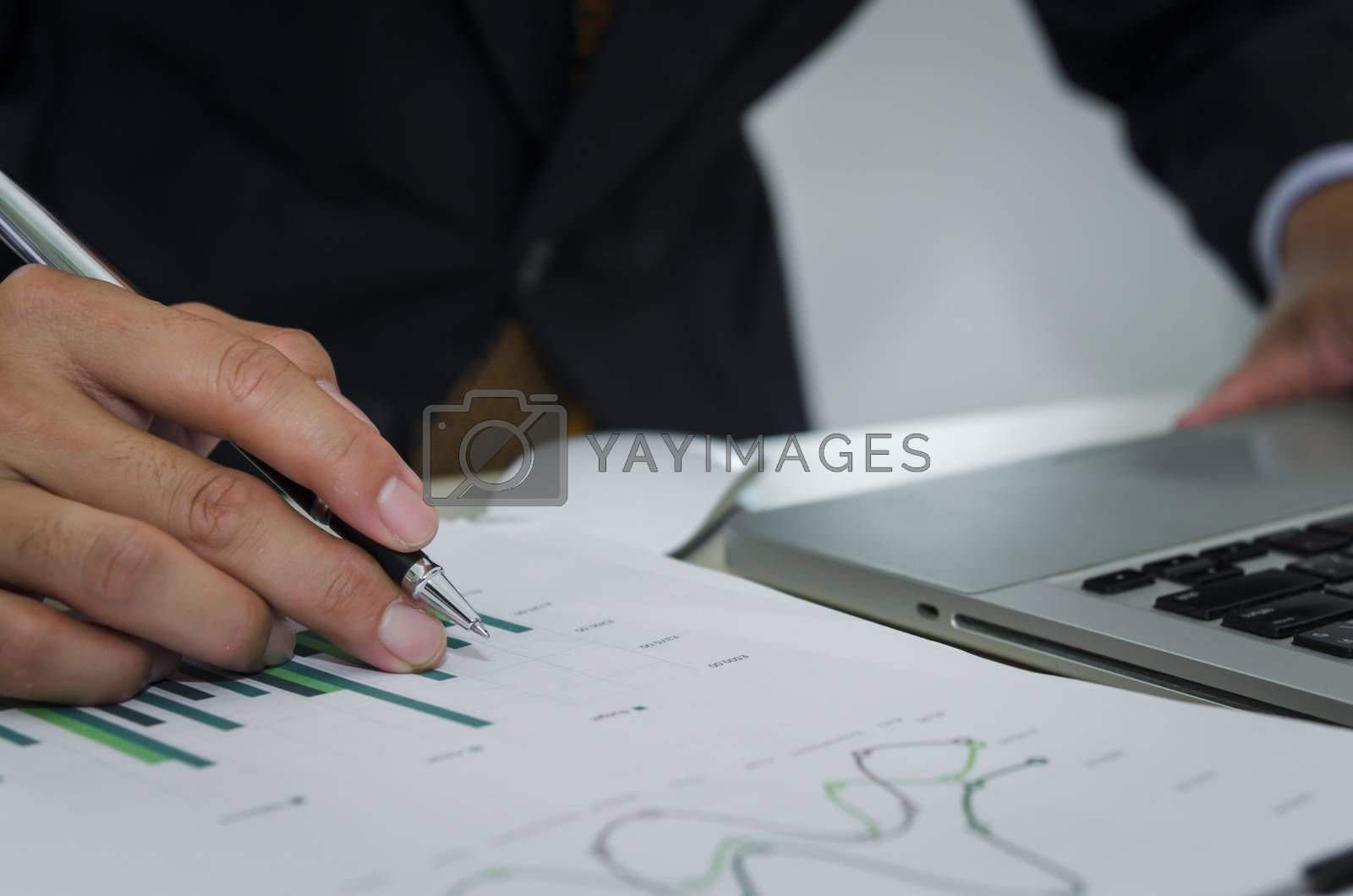 Business man holding a pen, business documents, reports, graphs and charts of financial statements and profit growth