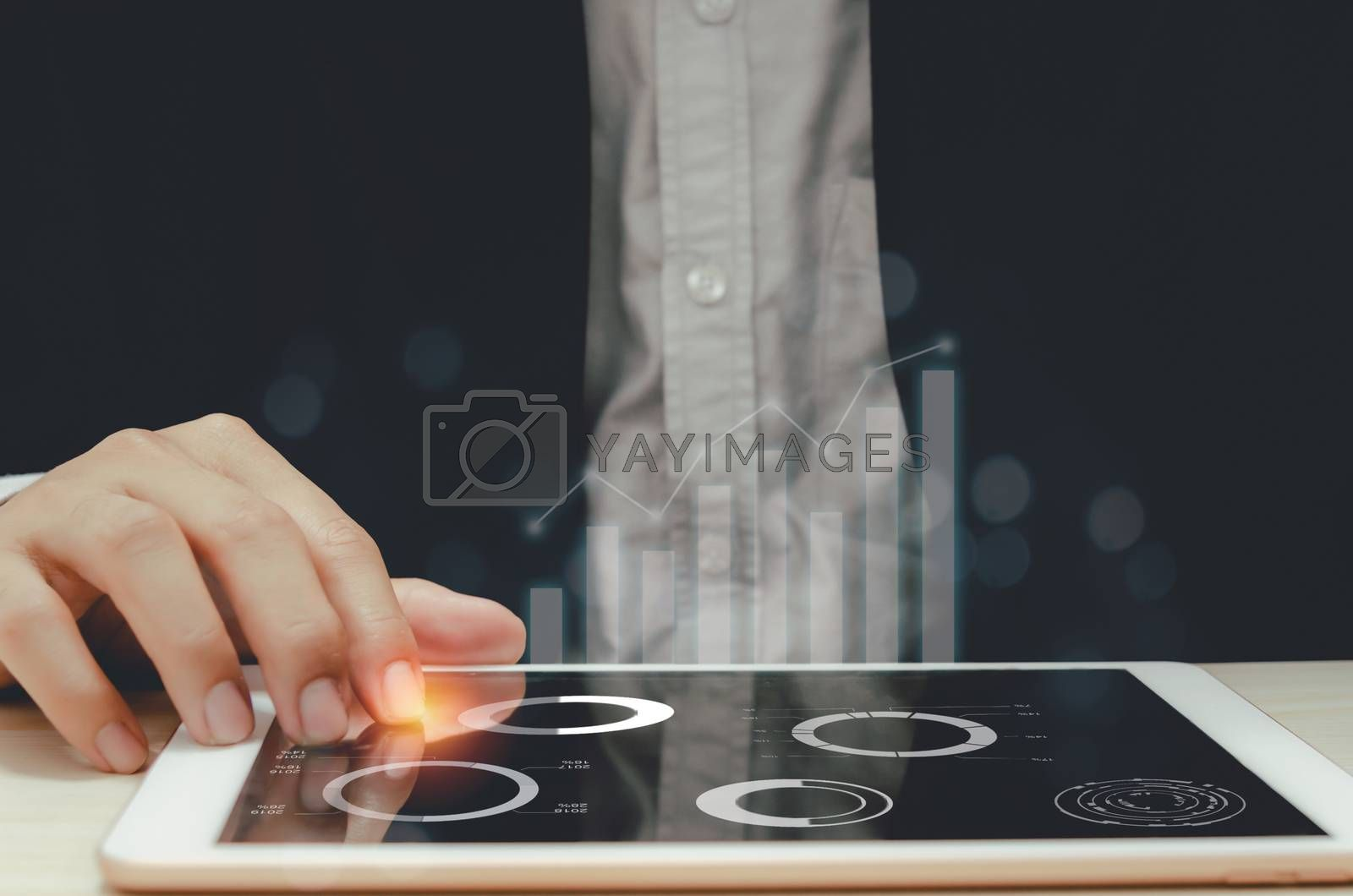 Businessman analyzing graphs and charts report profit and growth statistics in tablets.Focus hand