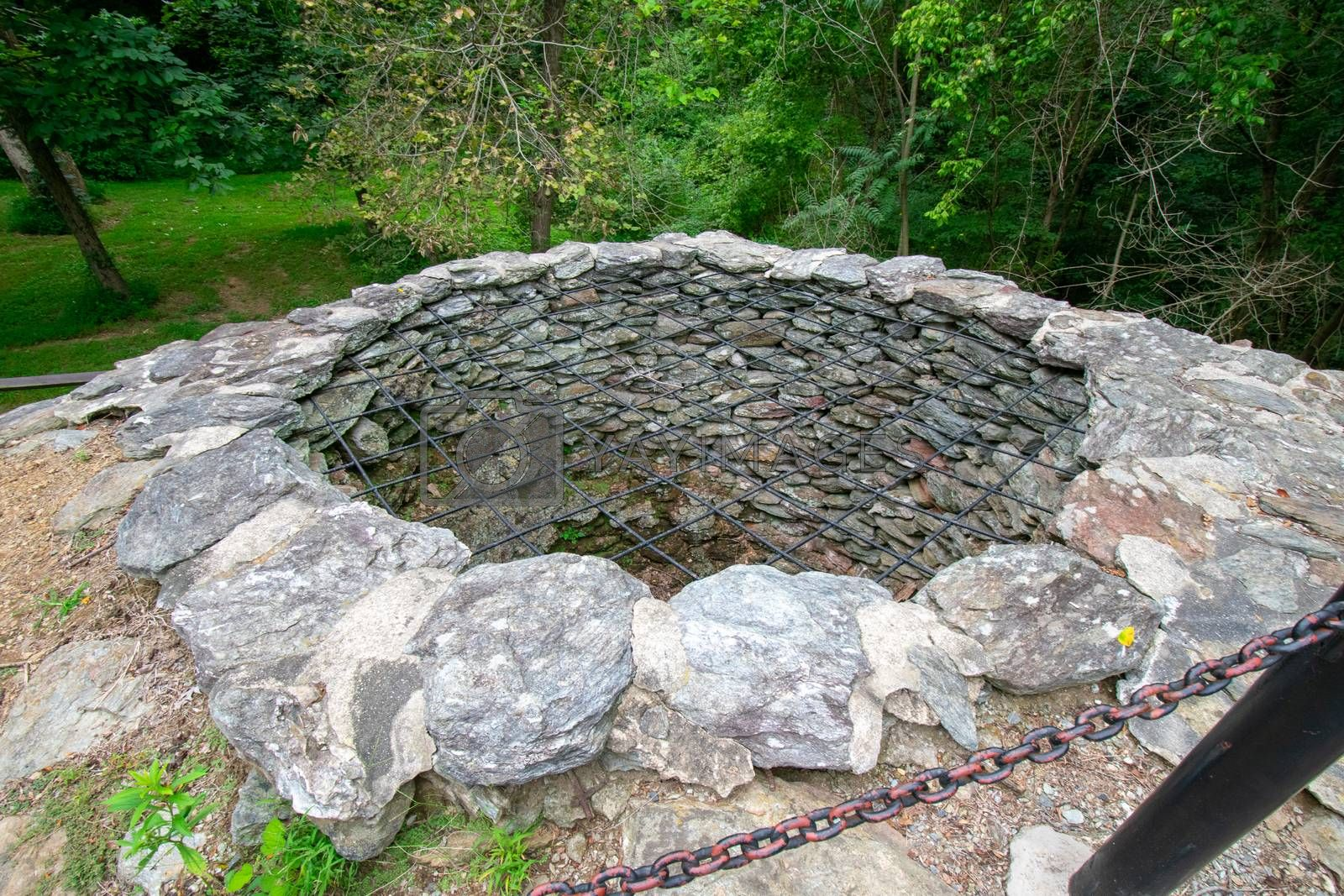 A Large Hole With Cobblestone Walls and a Metal Covering Over the Top at the Historic Lock 12 in Pennsylvania