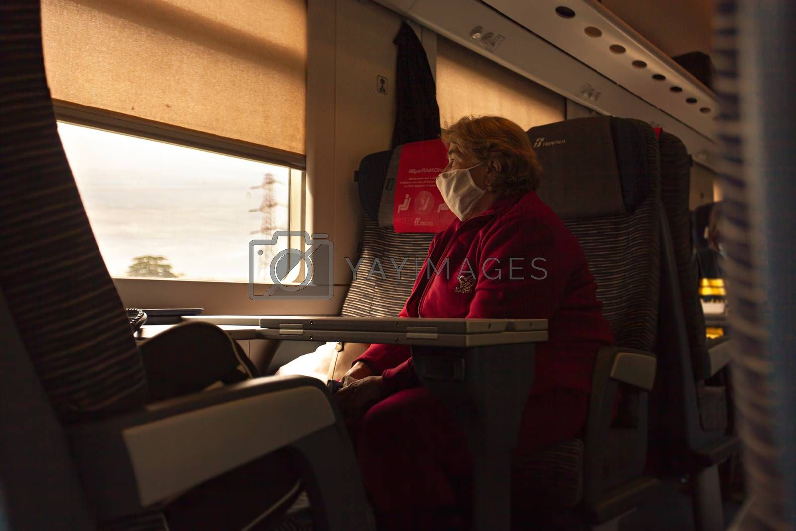 MODENA, ITALY 1 OCTOBER 2020: Old woman wears medical mask in train during Covid period