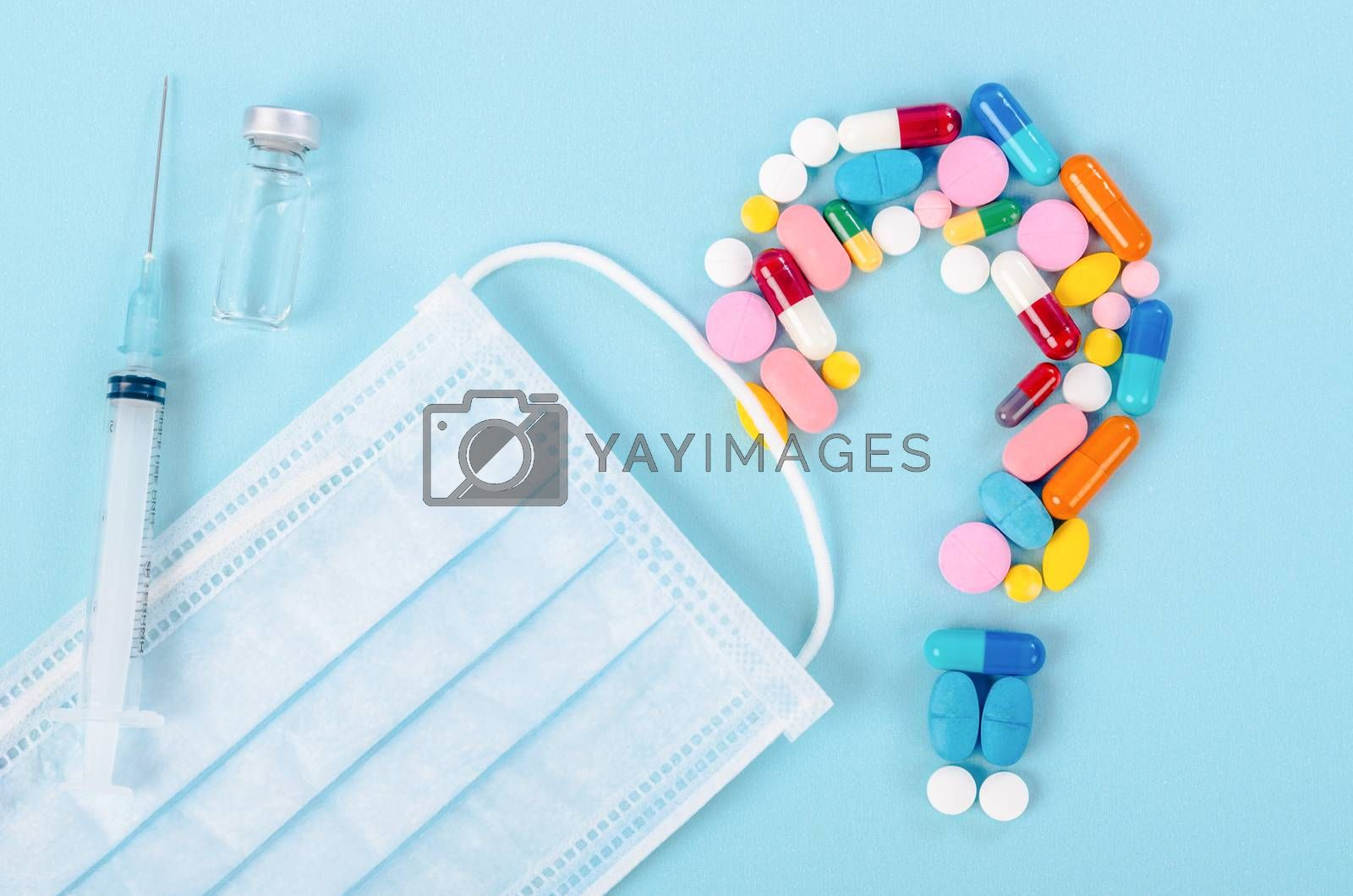 vaccine and pills with surgical mask on blue background.