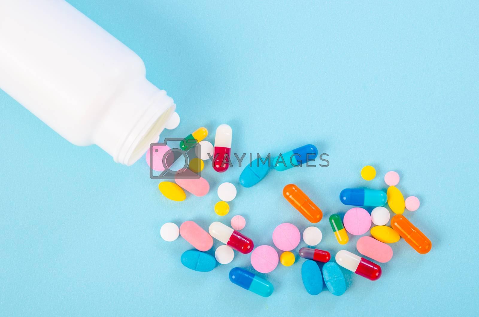 Medical pills and tablets spilling out of a drug bottle on blue background.