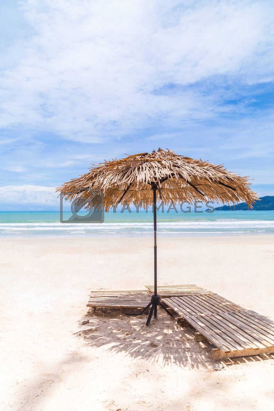Beach Umbrella made of palm leafs on a perfect white beach in front of Sea in Phuket Isaland, Thailand.