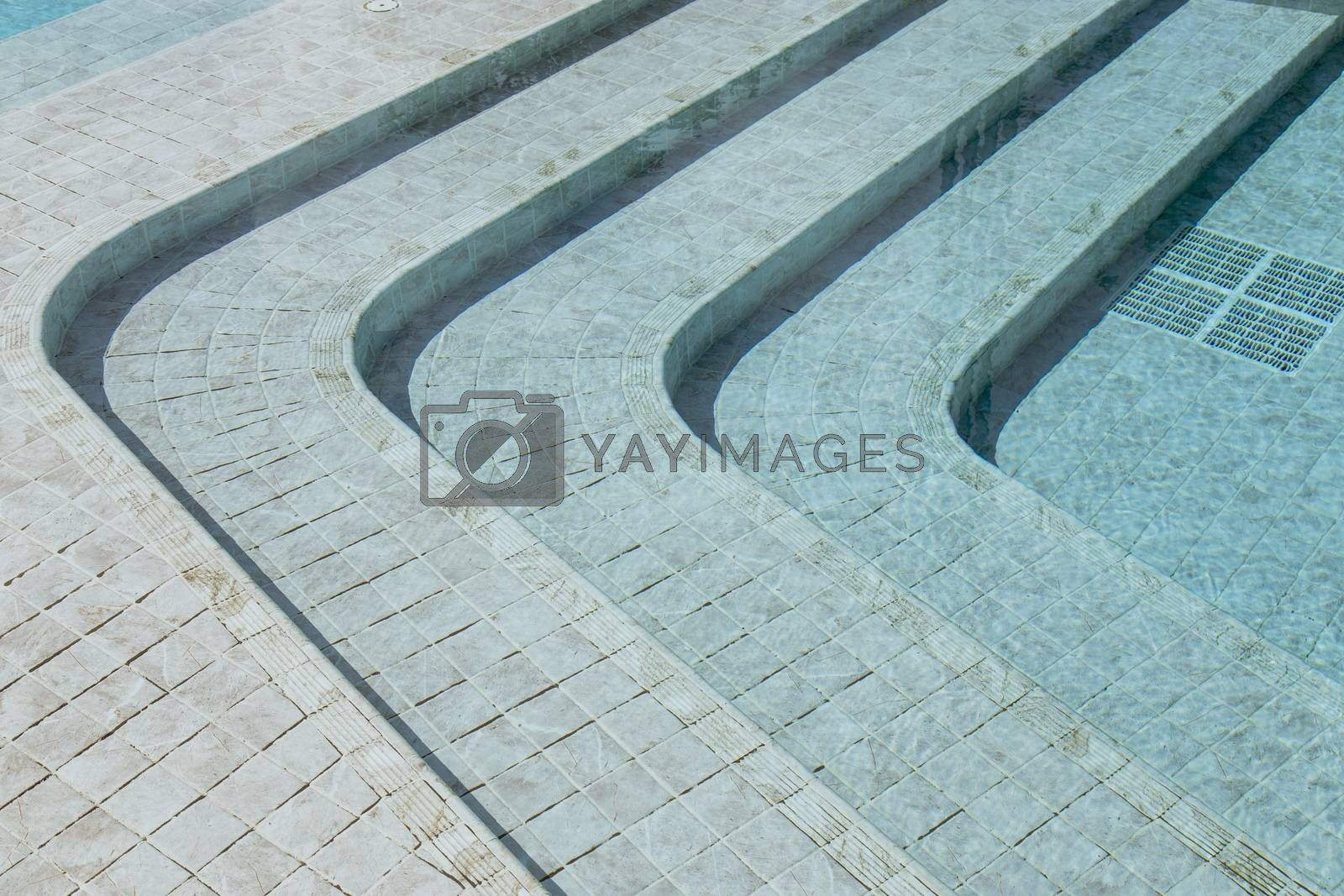 Curved steps at the swimming pool with blue tile mosaic