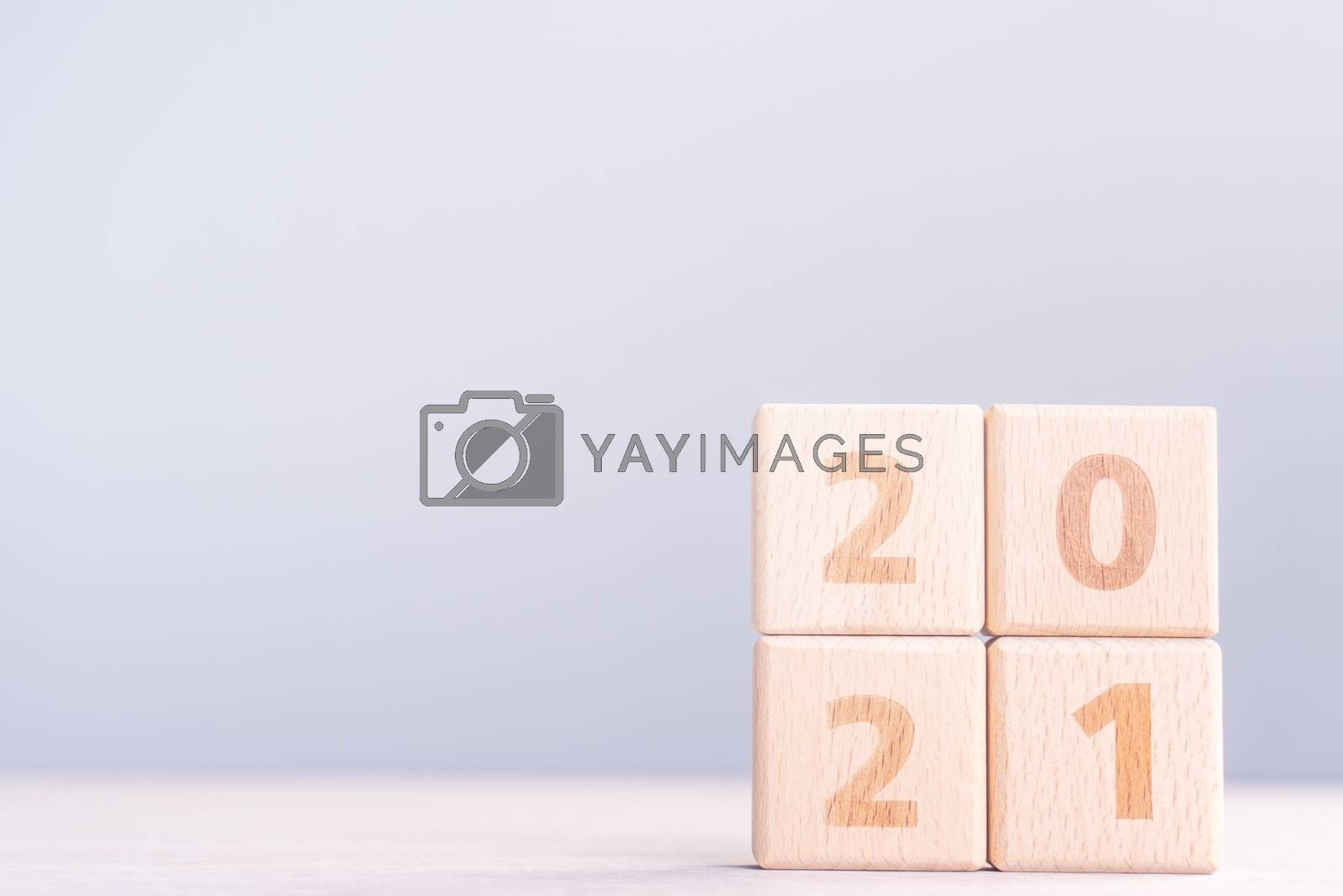 2021 New Year abstract design concept - Number wood block cubes isolated on wooden table and light mist blue background.