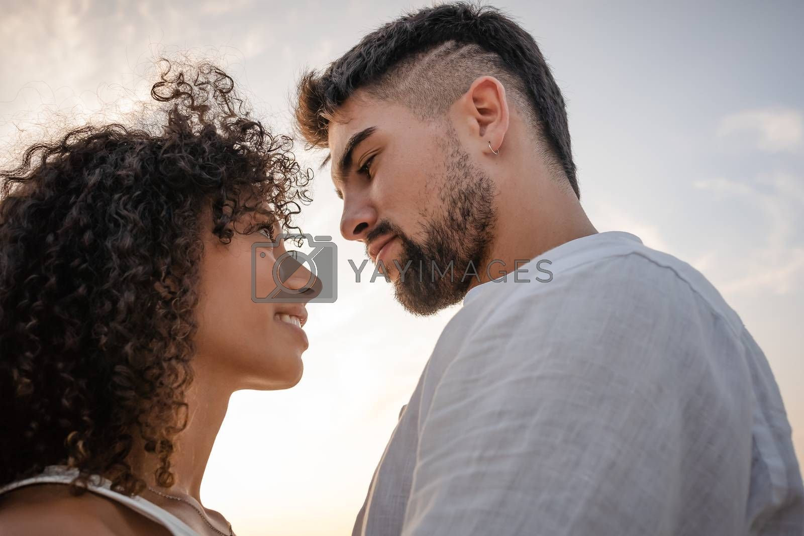Royalty free image of Side view of two young multiethnic passionate lovers looking in the eyes each other - Macho bearded sexy man looks at his Latin woman with ardor in a romance sunset scene ideal for a book cover by robbyfontanesi