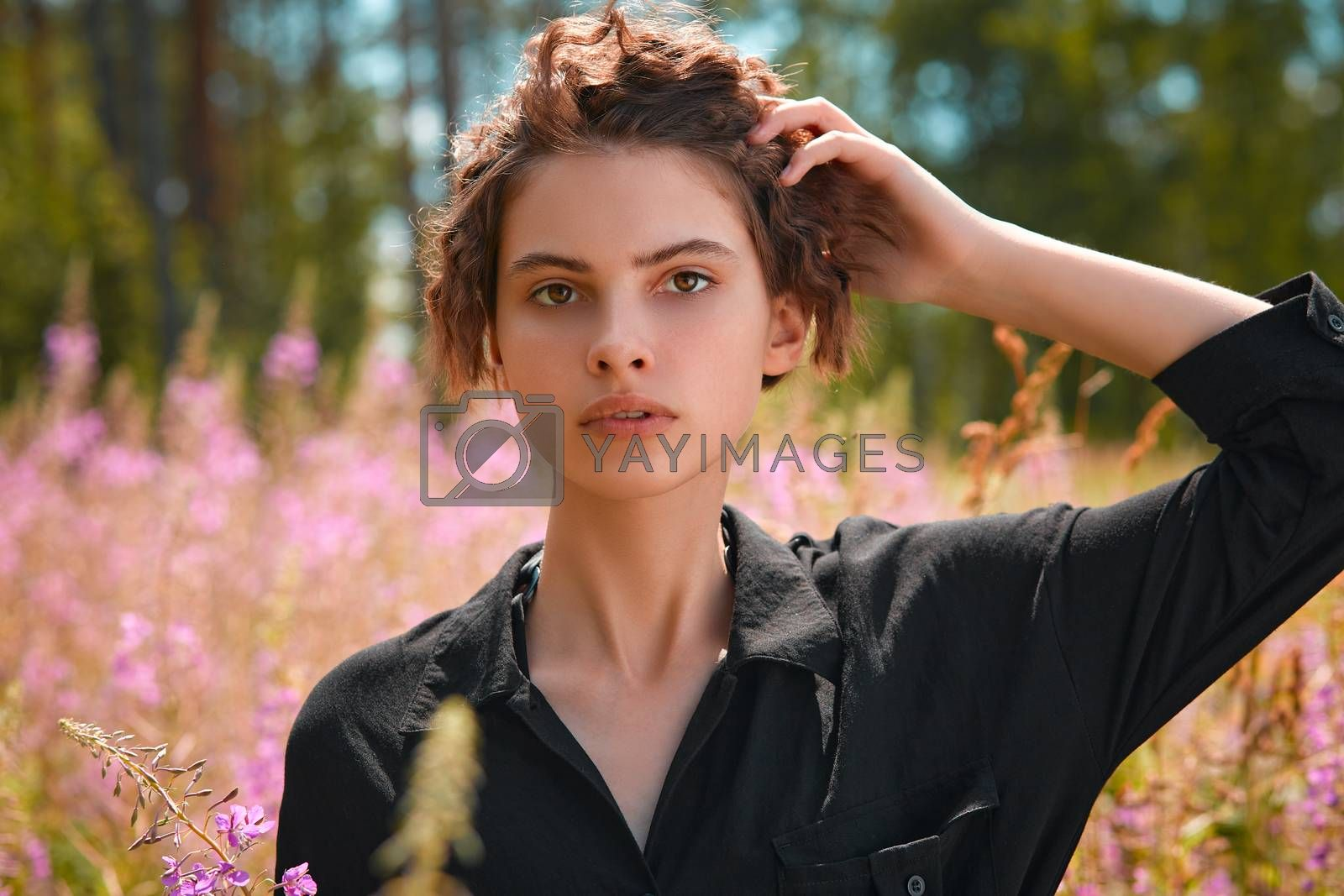 Beautiful young girl holding a bouquet of lupines in her hand. Soft focus
