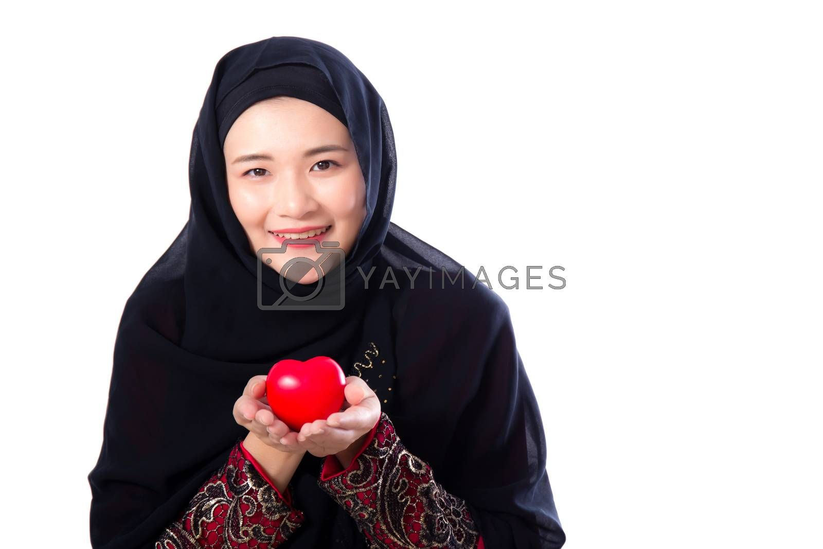 Portrait of young asian muslim woman holding red heart shaped pillow isolated on white background.