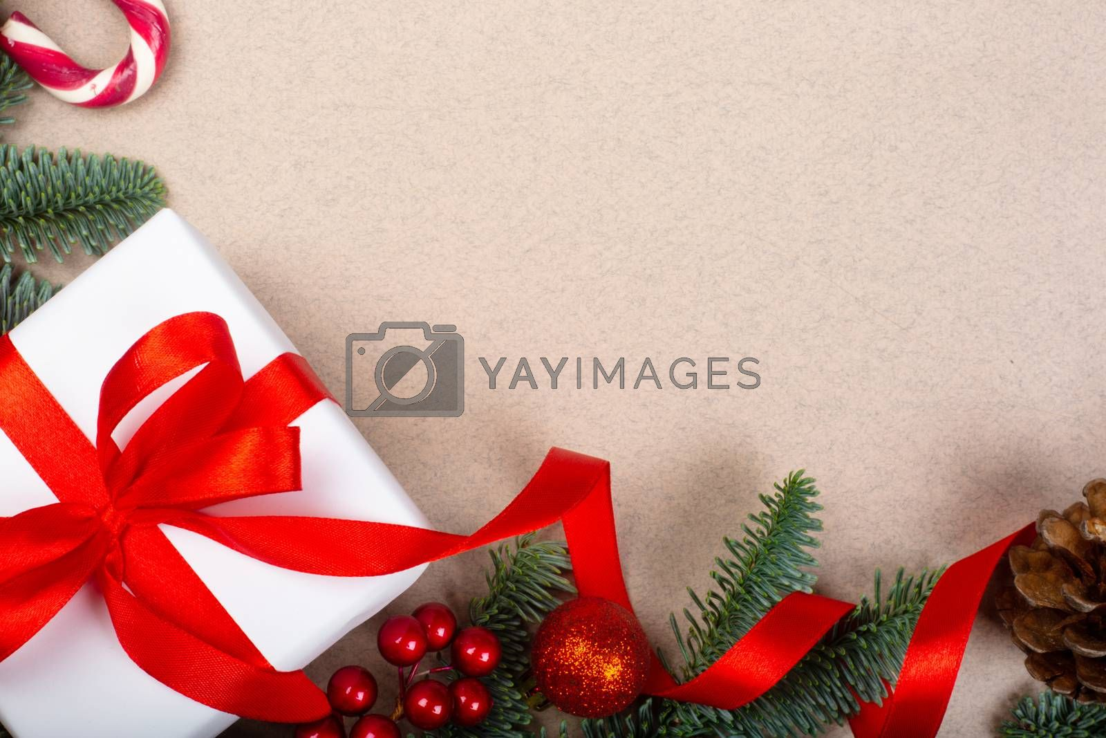 Traditional green christmas gift in white box with red ribbon bow tree noble fir cones and holly berries border frame on craft paper background copy space for text