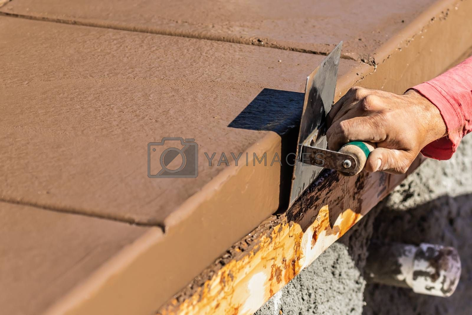Construction Worker Using Stainless Steel Edger On Wet Cement Forming Coping Around New Pool.