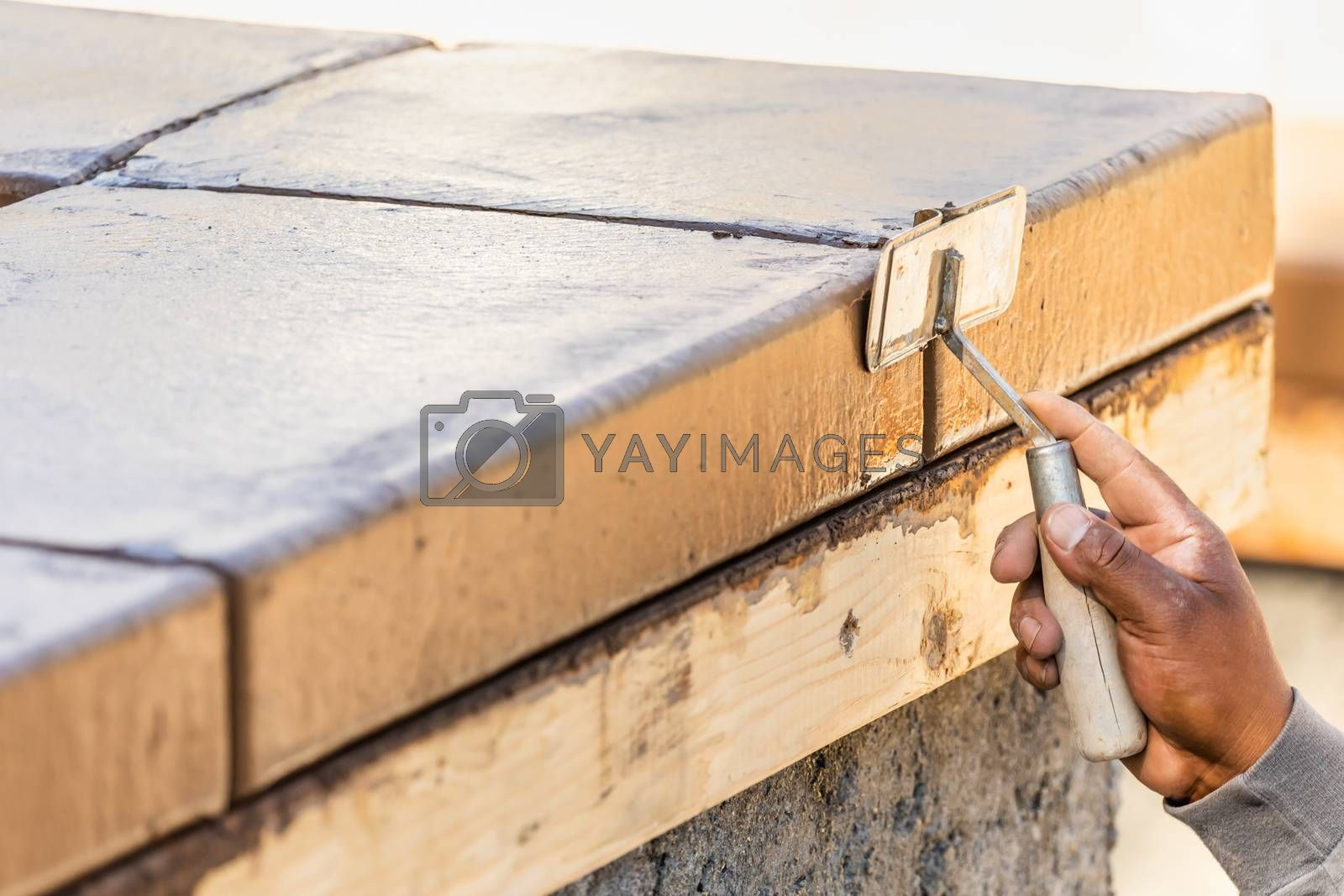 Construction Worker Using Hand Groover On Wet Cement Forming Coping Around New Pool.