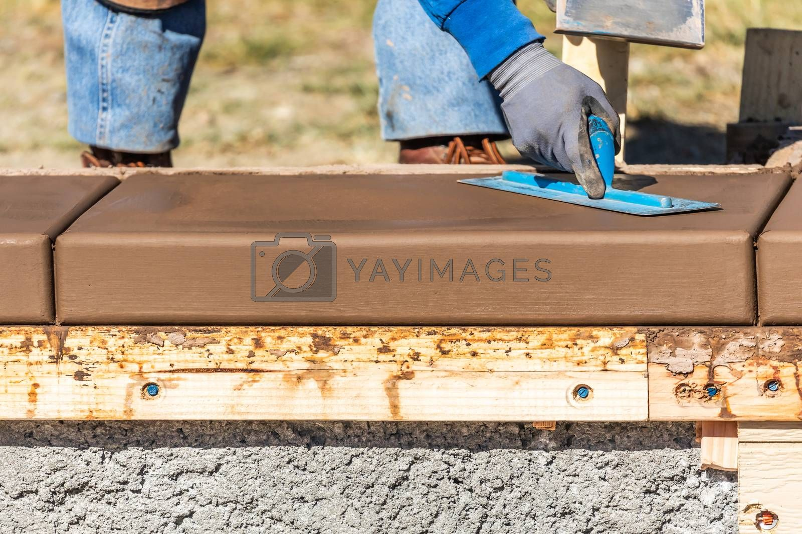 Construction Worker Using Trowel On Wet Cement Forming Coping Around New Pool.