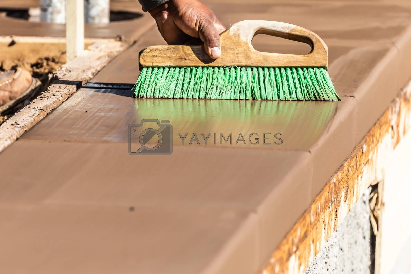 Construction Worker Using Brush On Wet Cement Forming Coping Around New Pool.
