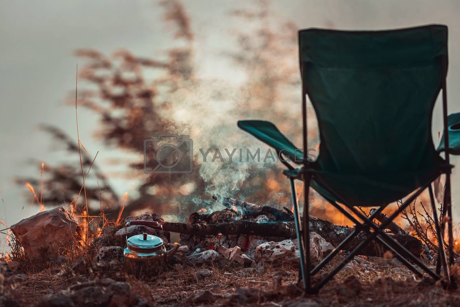 Conceptual Photo of an Autumnal Peaceful Recreation. Empty Camp Chair near Teapot in the Campfire. No People. Tranquility and Relaxation in the Nature.