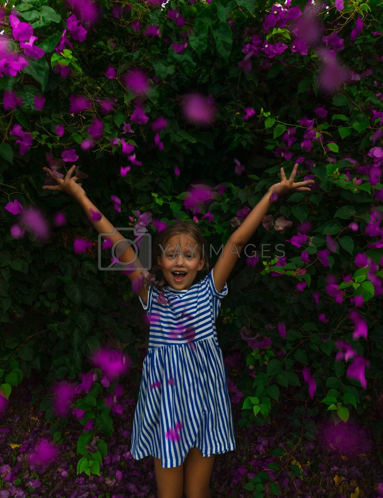 Cute Cheerful Little Girl with Raised Up Hands Enjoying Great Fresh Floral Bush. Summer Garden with Many Purple Flowers. Happy Healthy Childhood.