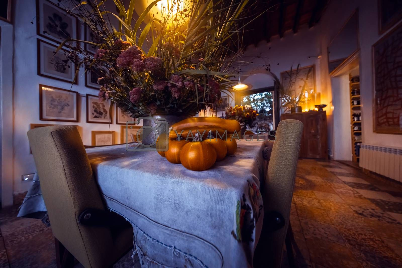 Thanksgiving Day in Family House. Festive Table with Pumpkins and Flowers Decoration. Traditional American Holiday. Autumn Harvest Celebration.
