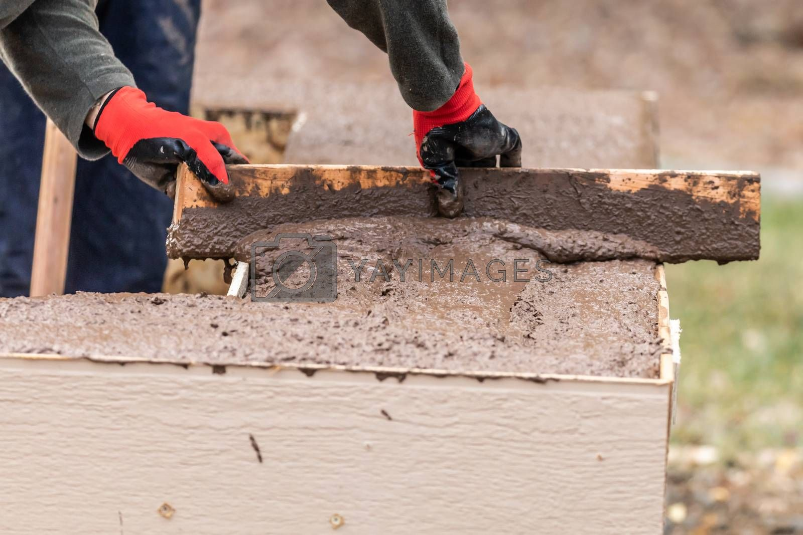 Construction Worker Leveling Wet Cement Into Wood Framing.