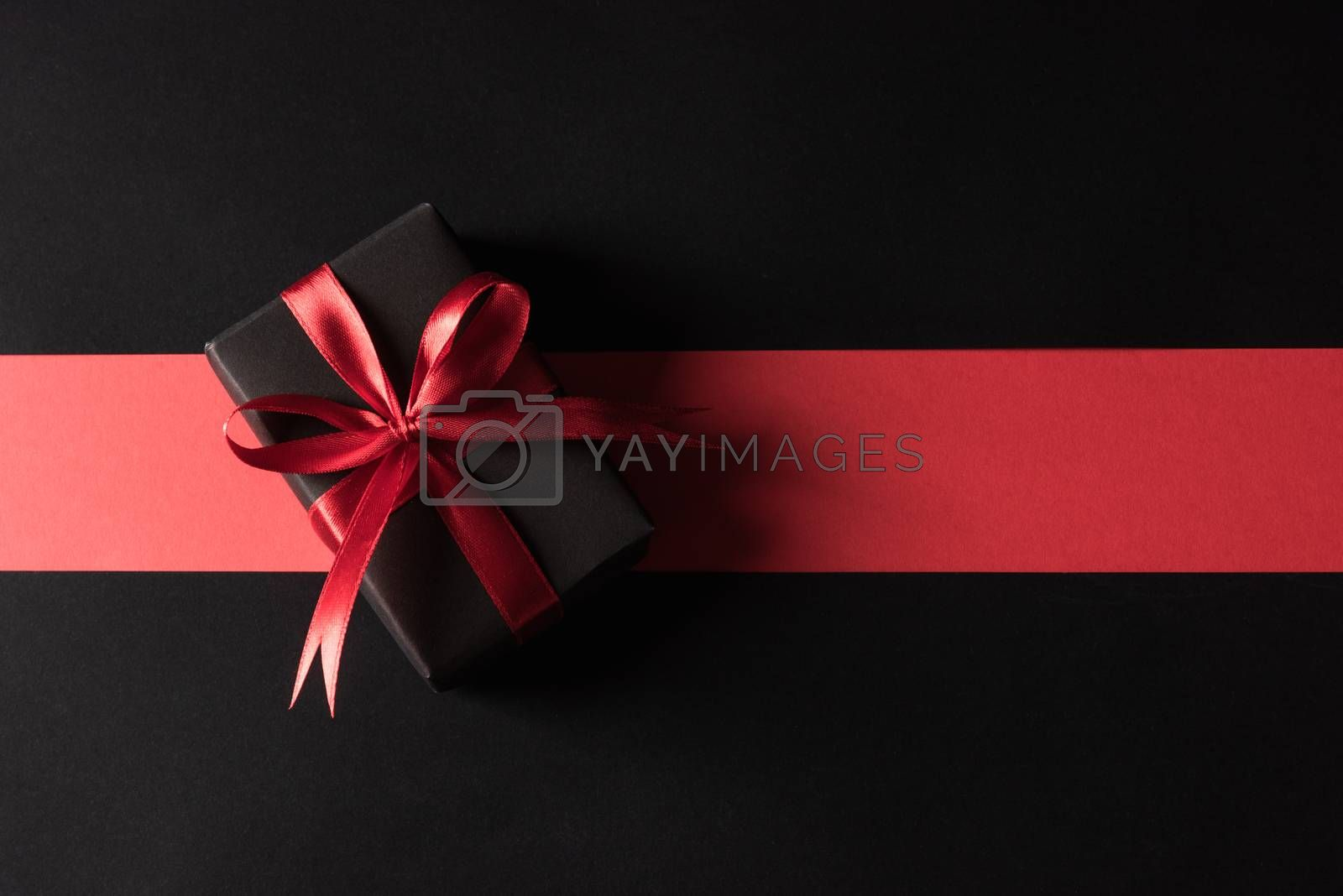 Black Friday sale shopping and Boxing Day concept, Gift box wrapped black paper and red bow ribbon present, studio shot isolated on red and dark background