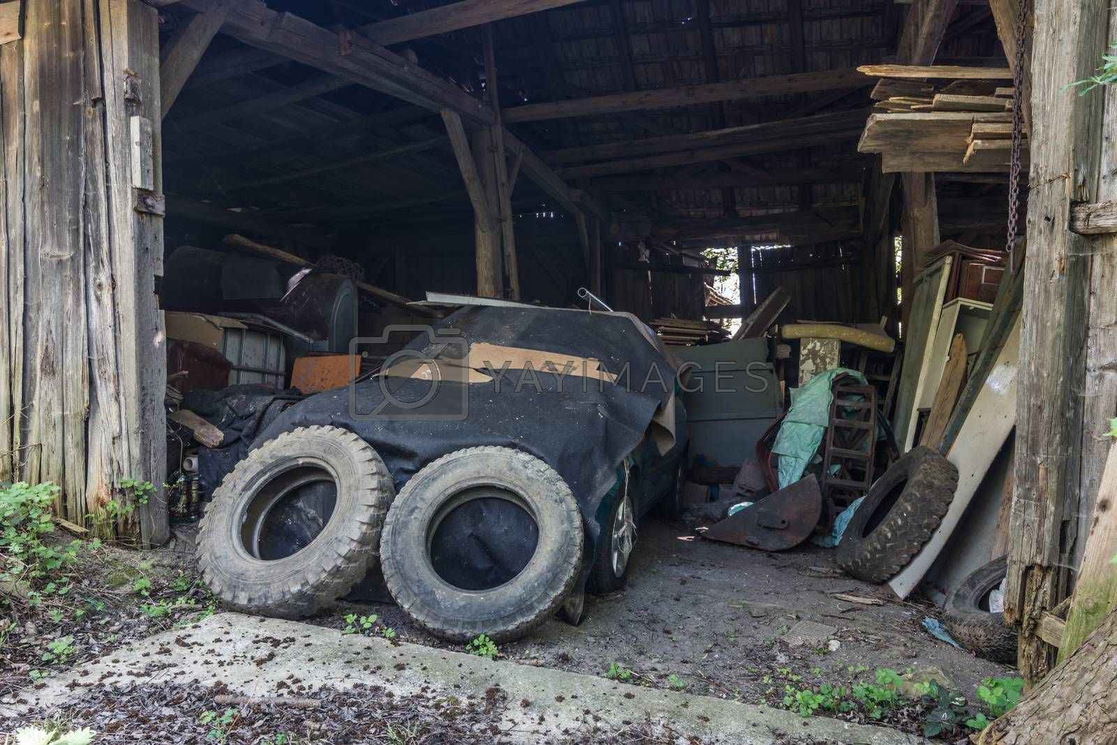 Car tire and old covered car in a barn