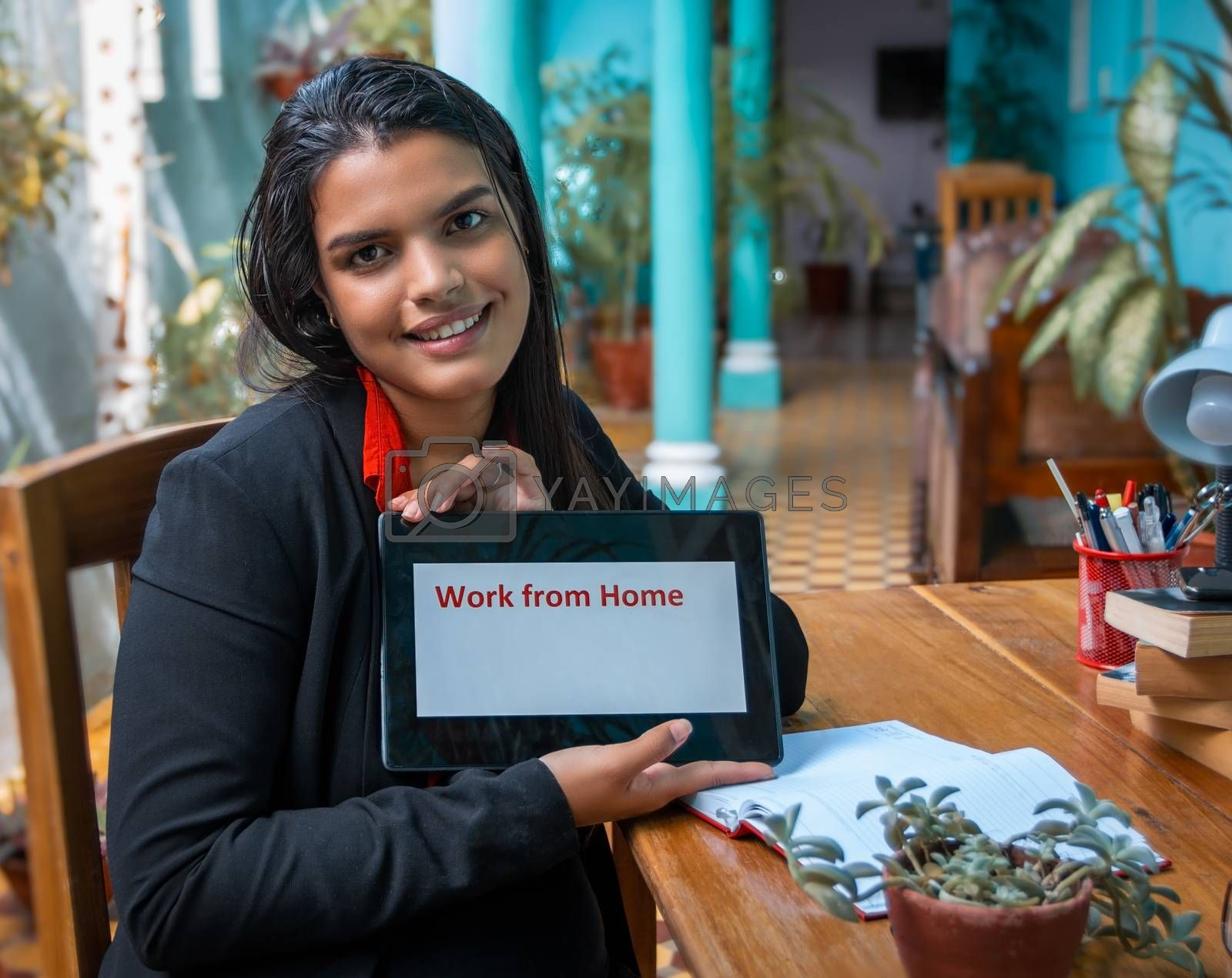 An smiling young woman sitting at a table with a tablet in her hands. On the tablet screen is written Work from home in red letters