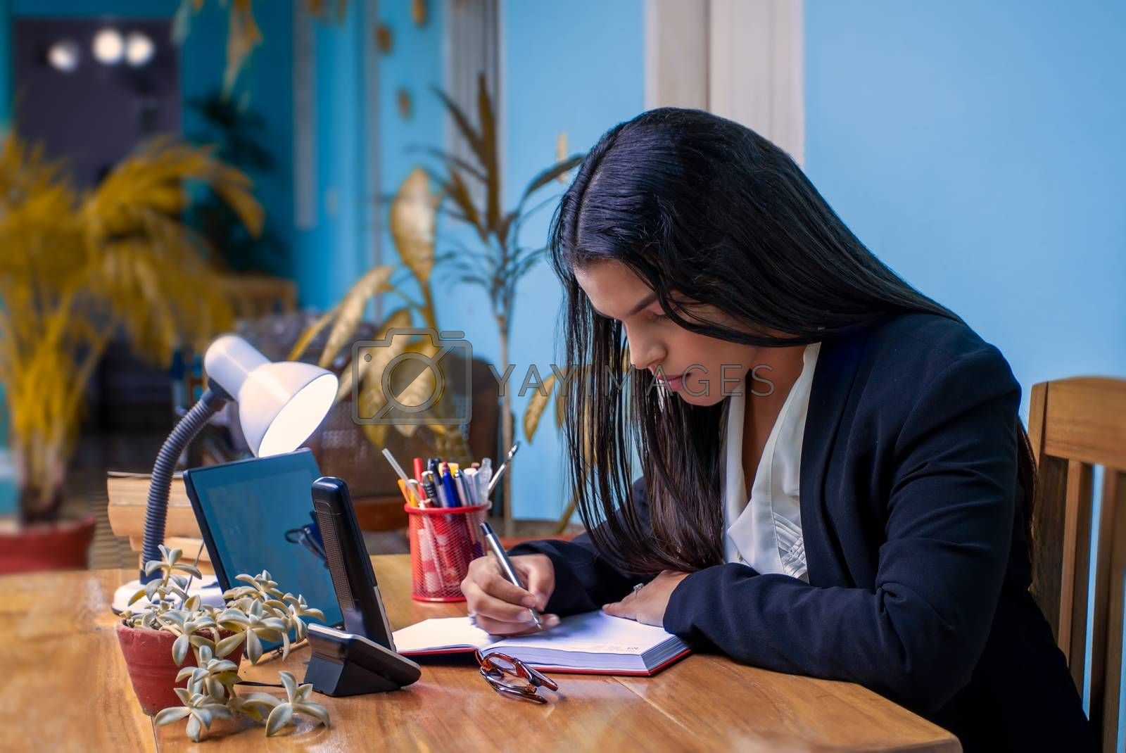 Young woman with long black hair at a desk writing in a notebook.
