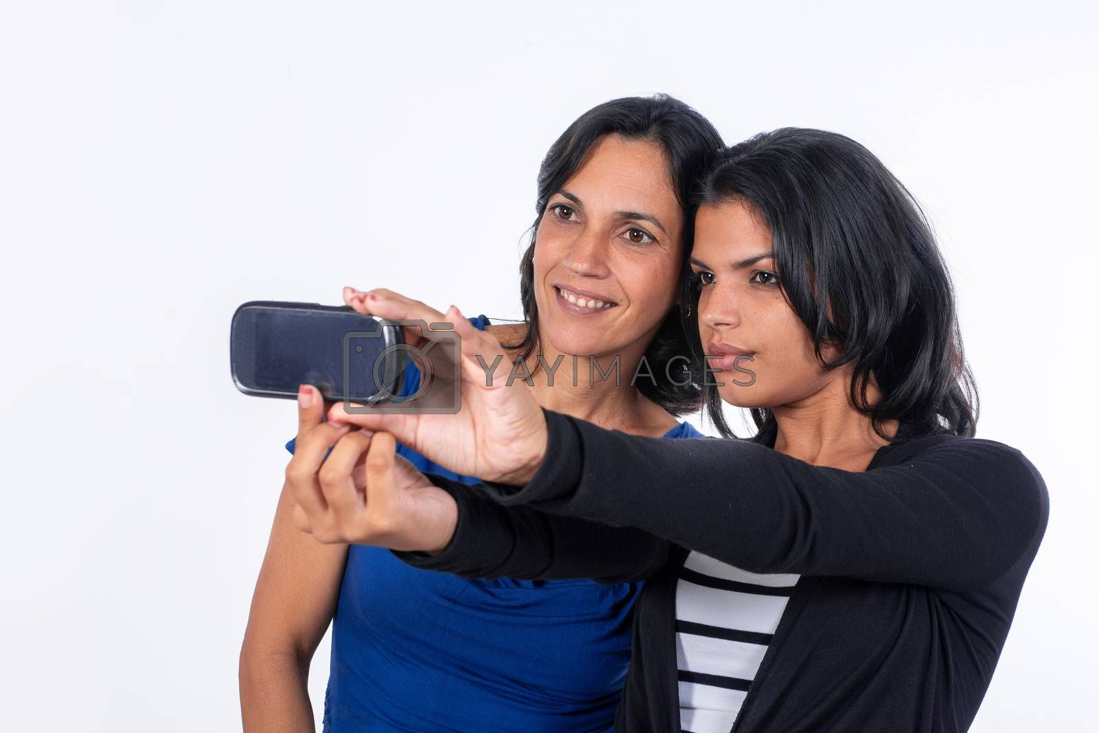 A woman and a girl taking a selfie with a cell phone. They both have black hair