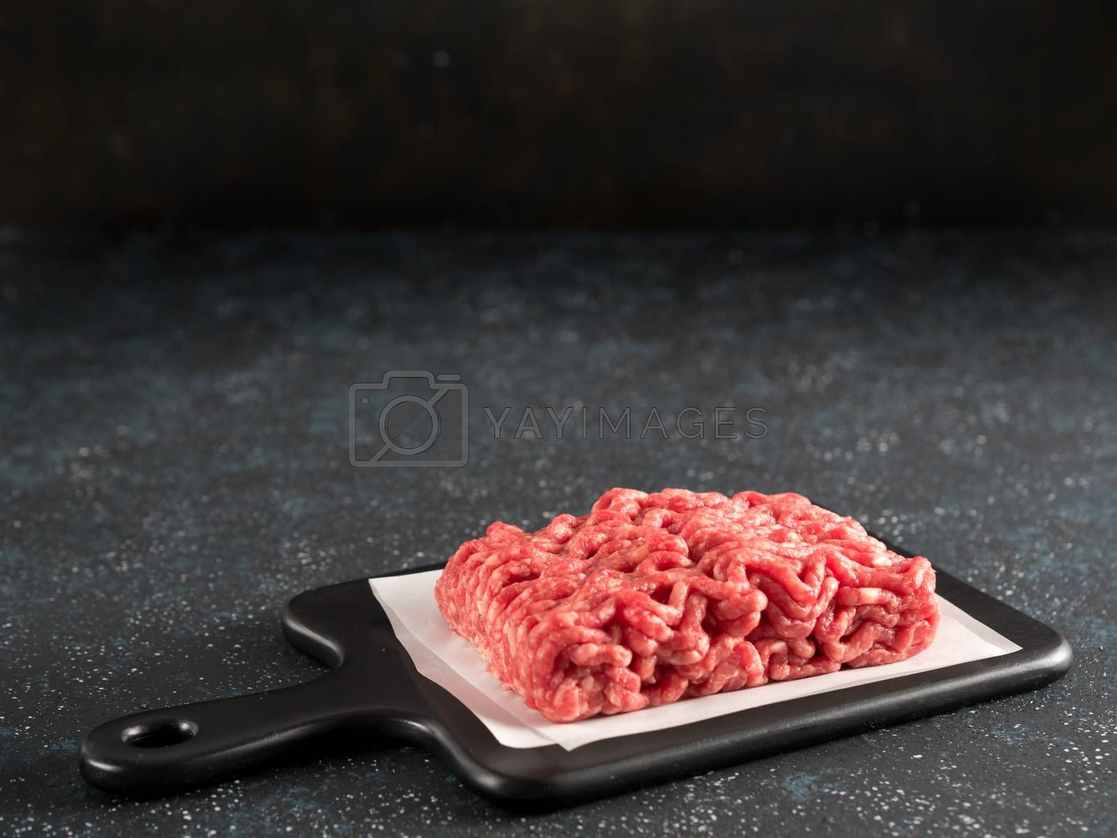 Fresh raw minced beef on backing paper and cutting board over black cement background with copy space.
