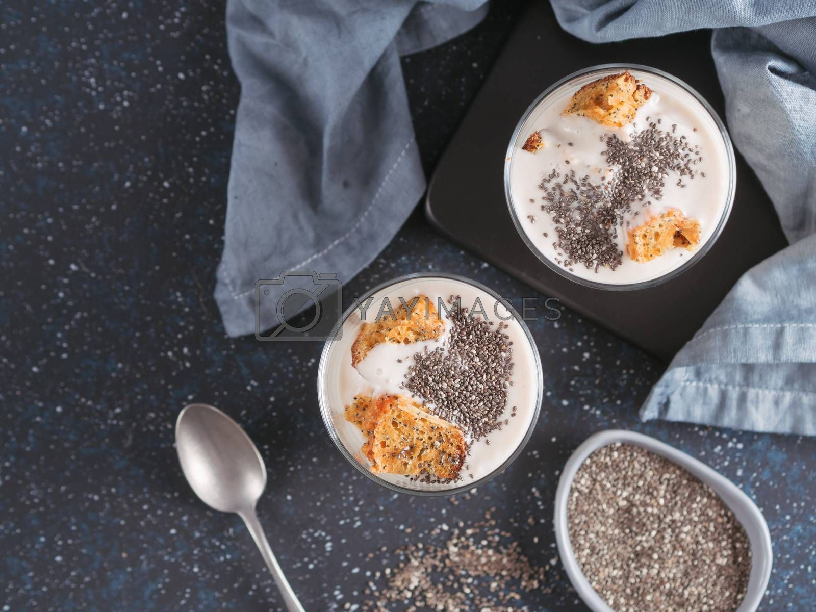 No baked cheesecake dessert with crushed carrots biscuits and chia seeds in glass jar on dark background. Ideas and recipes for healthy breakfast. Copy space for text. Top view or flat-lay.