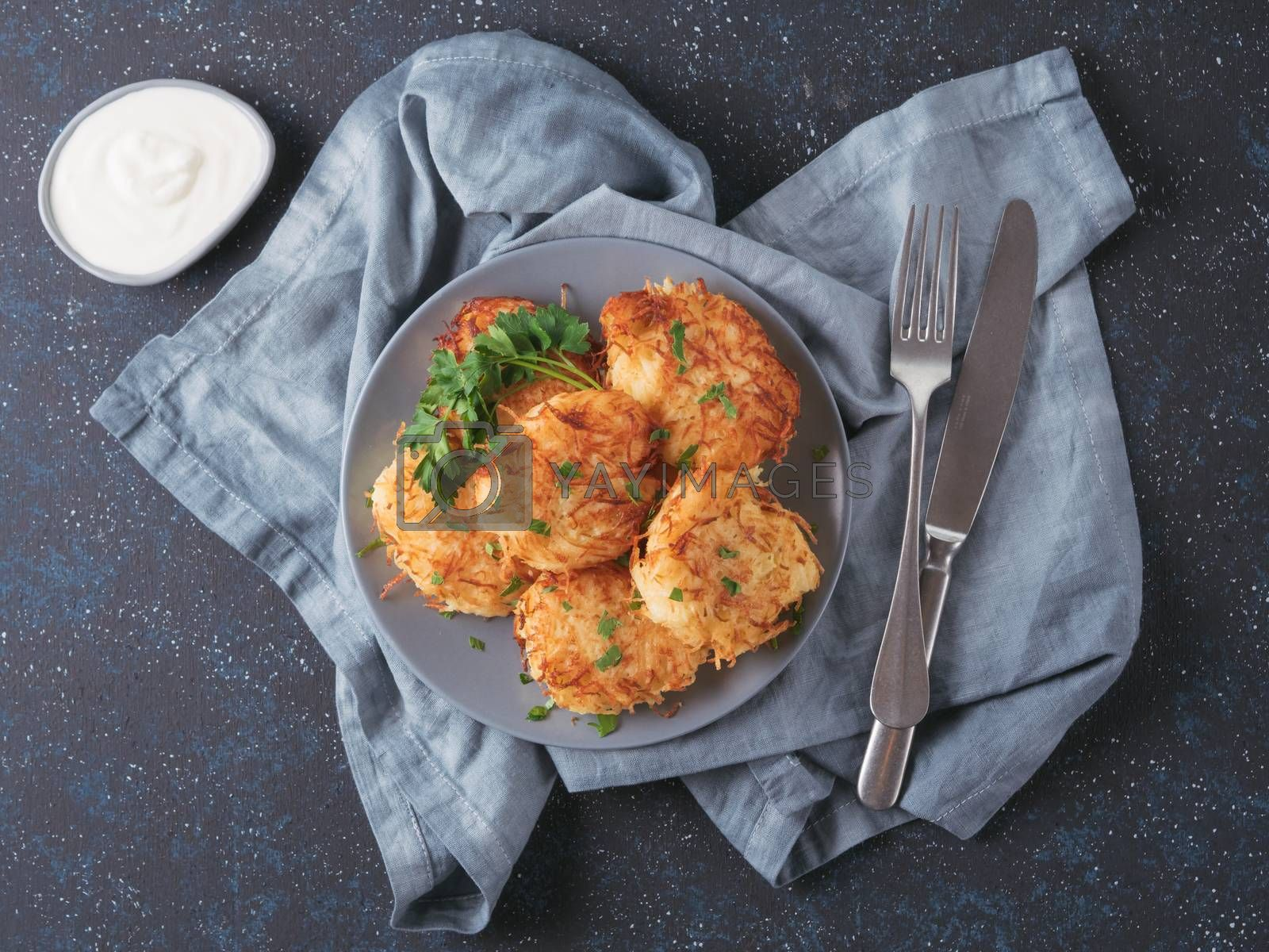 Close up view of potato pancakes. Potato flapjack on gray plate over dark blue background, with fresh parsley and sour cream. Copy space for text. Top view or flat-lay.