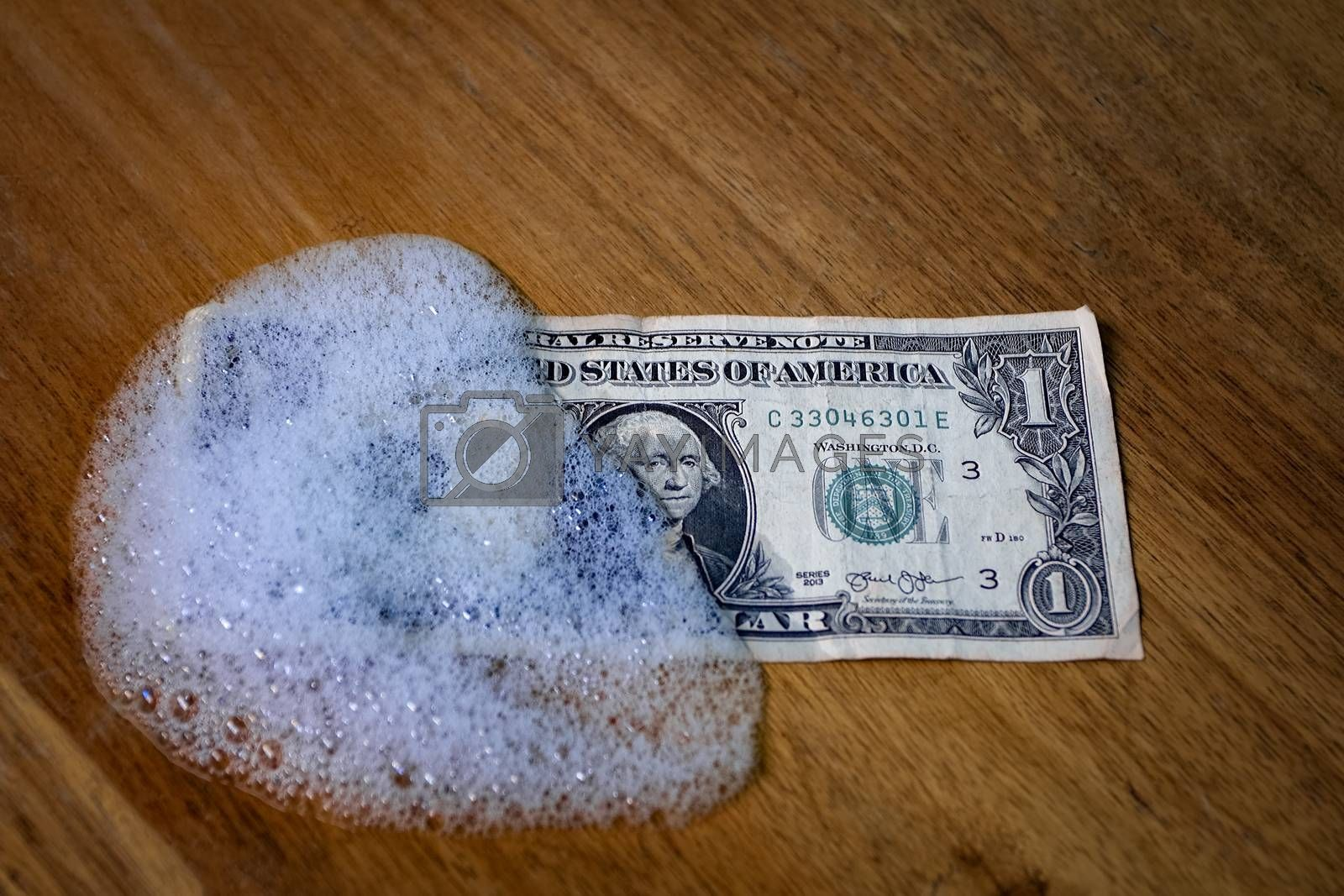 A one dollar bill partially covered by foam on a wooden surface