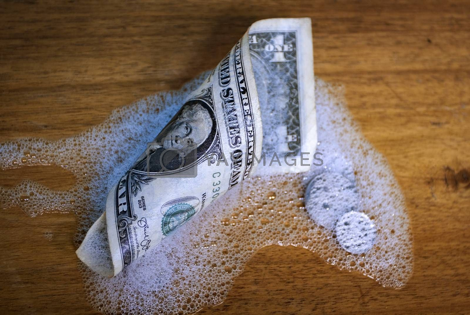 A rolled up dollar bill and coins, partially covered by foam on a wooden surface