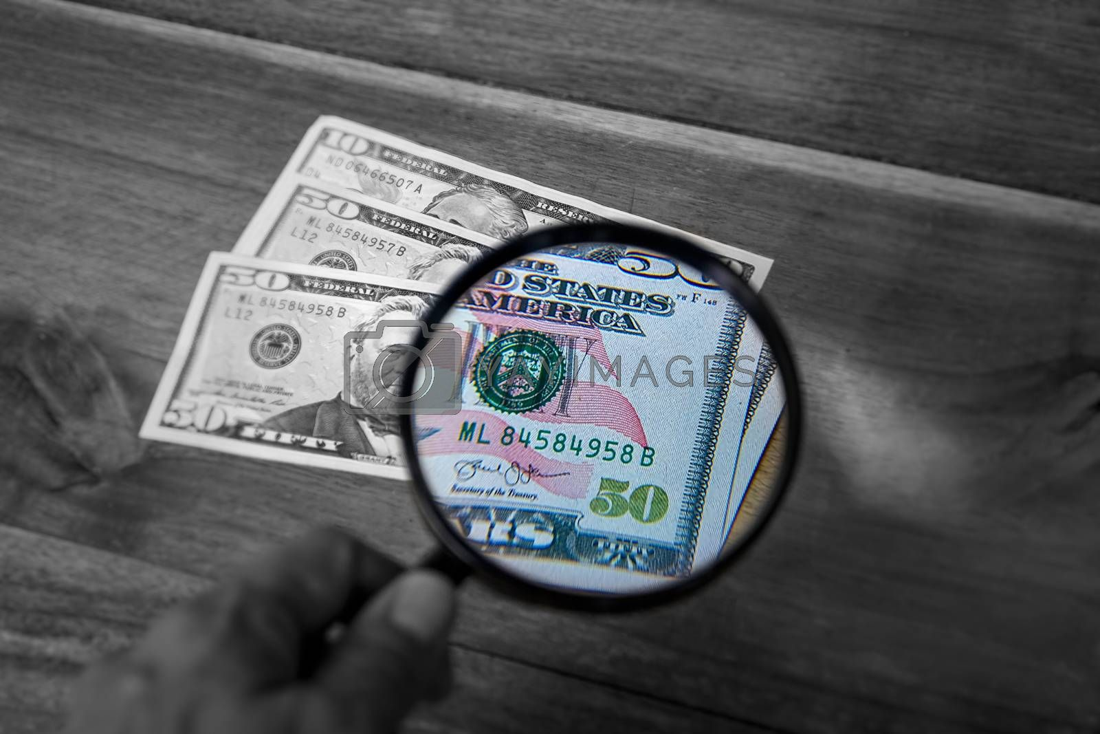 Partial view of a dollar through a magnifying glass. The part of the enlarged image is in color and the rest in black and white