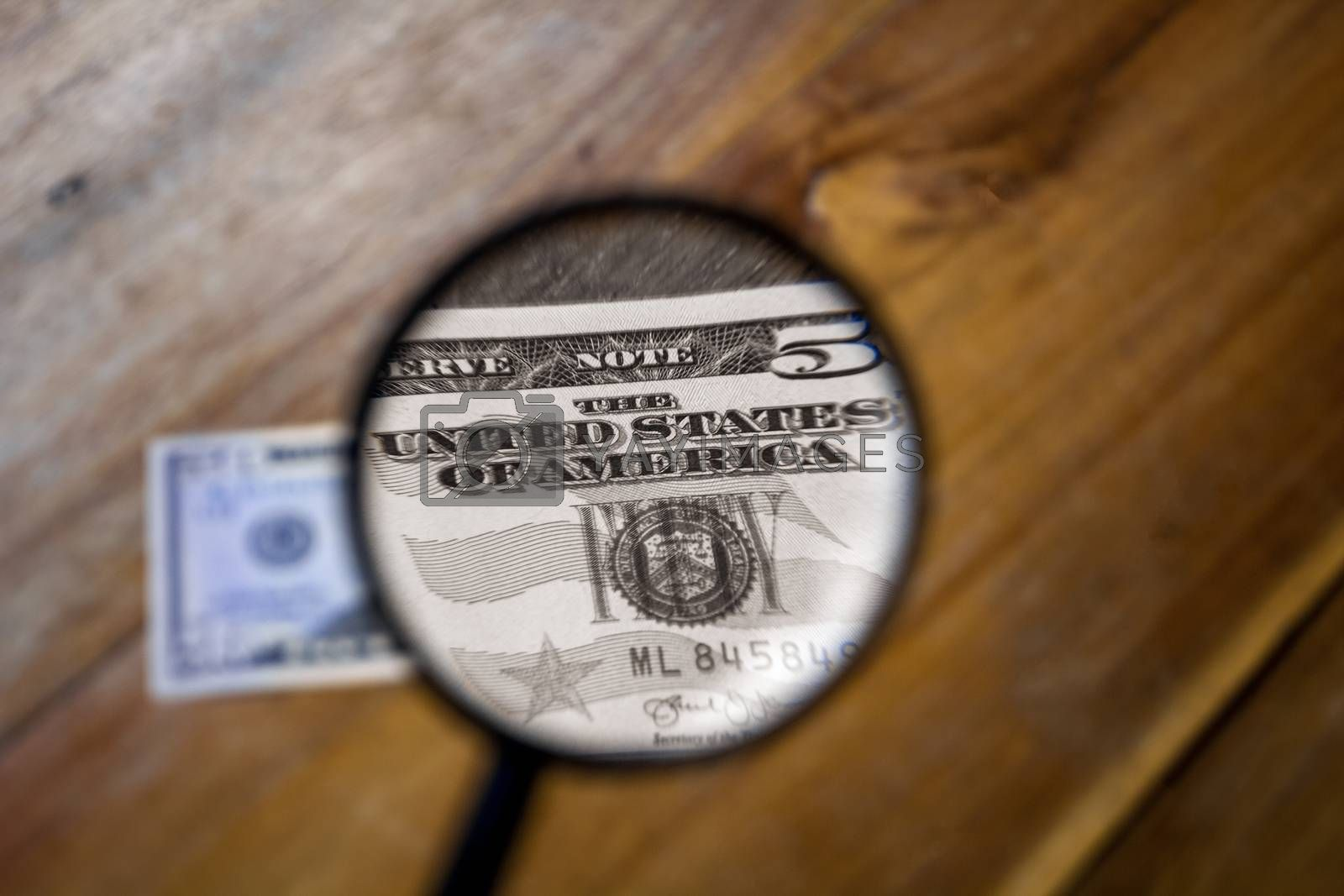 A colorless view through a magnifying glass of the letters, The United States of America, on a one dollar bill. The rest of the images are in color and out of focus.
