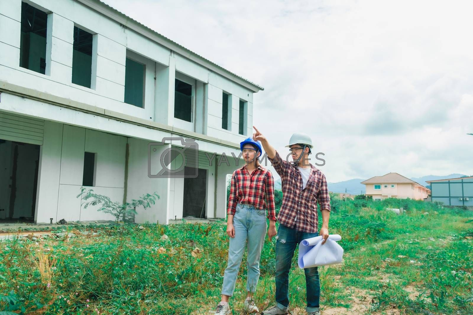 Young asian couple foreman engineering home inspection building house Walk home inspection with looking and pointing construction for check building home on job site to customers with new normol coronavirus covid-19