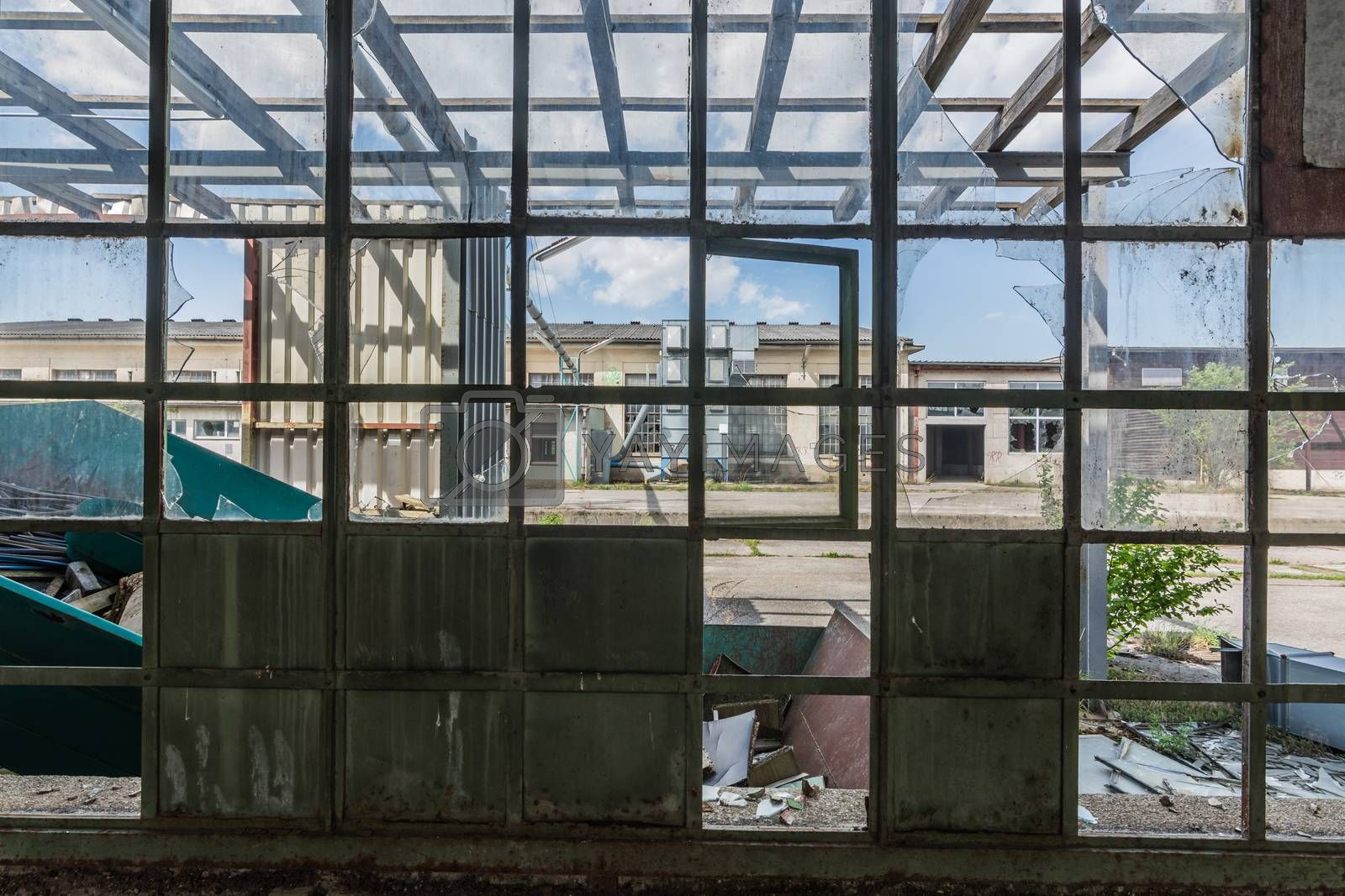 broken large window with a view of a factory building